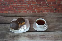 Twee donuts in chocoladesuikerglazuur en stukken van heemst liggen op een plaat dichtbij een kop thee Close-up stock afbeeldingen
