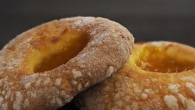 Twee donuts met abrikoos blokkeren op centrum een zwarte achtergrond stock fotografie