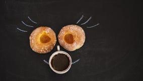 Twee donuts met abrikozenjam liggen en een Kop van koffie op een zwarte Raad stock afbeeldingen