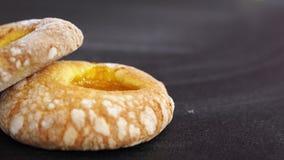 Twee donuts met abrikozenjam op de linkerzijde een zwarte achtergrond stock foto