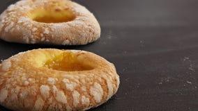 Twee doughnuts met gepoederde suiker en abrikozenjam leggen één voor één op de lijst stock afbeeldingen