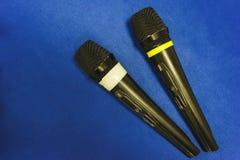 Twee draadloze microfoons liggen op een blauw bureau Radiomicrofoons voor het uitvoeren van een gebeurtenis en conferenties dicht Stock Fotografie
