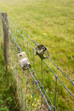 Twee draadspanners in een landbouwomheining Stock Fotografie