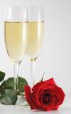 Twee drinkbekers shampagne en rood namen toe Stock Afbeeldingen