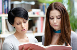 Twee droevige die studenten bij de bibliotheek worden gelezen Stock Afbeeldingen