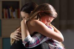 Twee droevige tienerjaren die bij slaapkamer omhelzen stock foto