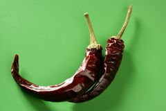 Twee droge peper, Spaanse peper, over groene achtergrond Stock Fotografie