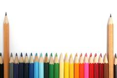 Twee eenvoudige houten potloden onder kleurenpotloden Stock Fotografie
