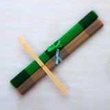 Twee eetstokjes op bamboematten stock foto's