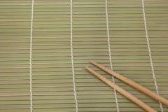 Twee eetstokjes op een achtergrond van de bamboemat stock afbeelding
