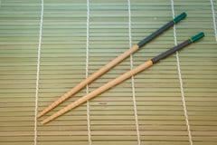 Twee eetstokjes op een achtergrond van de bamboemat stock afbeeldingen
