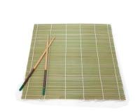 Twee eetstokjes op een achtergrond van de bamboemat stock fotografie