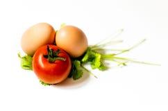 Twee eieren en een tomaat op een blad van Parshley Stock Fotografie