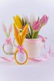 Twee eieren van het konijntjesservet voor Pasen en bloemen op witte achtergrond Stock Afbeelding