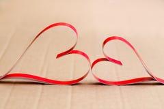 Twee eigengemaakte document rode harten op een beige kartonachtergrond, het symbool van de Dag van Valentine royalty-vrije stock afbeeldingen