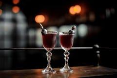 Twee elegante die glazen met de verse zoete en sterke cocktail van de zomerarnaud op de donkere vage achtergrond van bar worden g Royalty-vrije Stock Foto's
