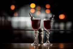Twee elegante die glazen met de verse zoete en sterke cocktail van de zomerarnaud op de donkere vage achtergrond worden gevuld Stock Afbeelding