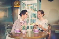 Twee elegante jonge dames in een koffie stock afbeeldingen