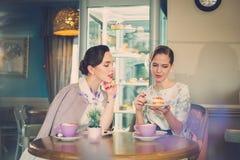 Twee elegante jonge dames in een koffie royalty-vrije stock fotografie