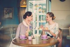 Twee elegante jonge dames in een koffie royalty-vrije stock afbeeldingen