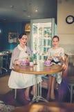 Twee elegante jonge dames in een koffie stock fotografie