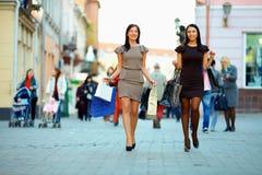 Twee elegante vrouwen die in overvolle stad winkelen Stock Afbeeldingen