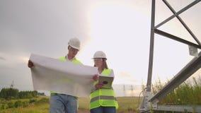 Twee elektriciens werken samen, zich bevindt op het gebied dichtbij de lijn van de elektriciteitstransmissie in helmen Status in stock videobeelden