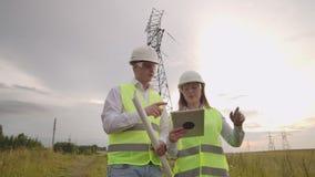 Twee elektriciens werken samen, zich bevindt op het gebied dichtbij de lijn van de elektriciteitstransmissie in helmen Status in stock footage