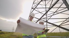 Twee elektriciens werken samen, zich bevindt op het gebied dichtbij de lijn van de elektriciteitstransmissie in helmen Status in stock video