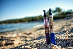 Twee Elektronische die Sigaretten in zand worden geplakt Stock Foto's
