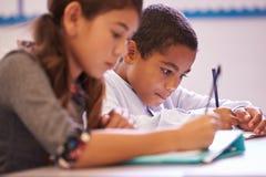 Twee elementaire scholieren die bij bureau tijdens een les werken stock foto's