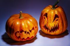 Twee enge Halloween-pompoenen met schaduwen op een gekleurde backgrou royalty-vrije stock afbeeldingen