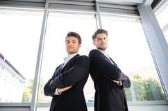 Twee ernstige jonge zakenlieden die zich met die wapens bevinden in bureau worden gekruist royalty-vrije stock afbeelding