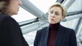 Twee ernstige vrouwelijke onderneemsters lopen en bespreken Zaken Zij allen werken in centraal bedrijfsdistrict stock footage