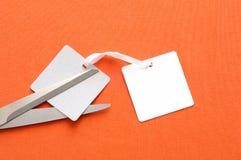Twee etiketten op oranje doek, een schaar snijden één, een concept voor bedelaars stock afbeeldingen