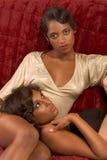 Twee etnische sexy vrouwen op bank in retro kleren Stock Afbeelding