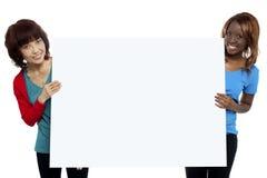Twee etnische vrouwelijke modellen die whiteboard voorstellen royalty-vrije stock fotografie