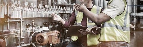Twee fabrieksarbeiders die terwijl de controle productielijn drinkt bespreken royalty-vrije stock fotografie