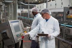 Twee fabrieksingenieurs die machine in fabriek in werking stellen royalty-vrije stock afbeelding