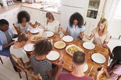 Twee Families die Grace Before Eating Meal Together zeggen stock foto