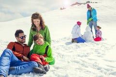 Twee families die pret in de sneeuw in berg hebben royalty-vrije stock foto's