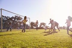 Twee families die van een voetbalspel met hun kinderen genieten stock foto