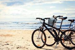 Twee fietsen die zich op het strandzand bevinden op overzeese kustlijn stock foto