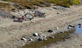 Twee fietsen liggen op de zandige kust met stenen dichtbij de stroom royalty-vrije stock foto's