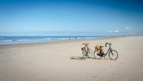 Twee fietsen op het Schiermonnikoog-strand die op hun eigenaars wachten Stock Afbeeldingen