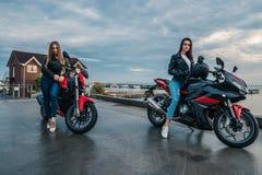 Twee Fietsermeisjes in leerjasjes op de motorfietsen van een zwarte en rode kleurensport Royalty-vrije Stock Foto's