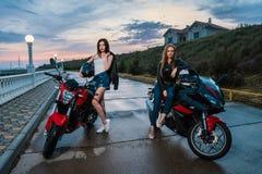 Twee Fietsermeisjes in leerjasjes op de motorfietsen van een zwarte en rode kleurensport Royalty-vrije Stock Afbeelding