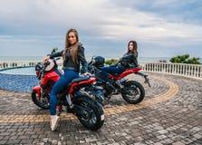 Twee Fietsermeisjes in leerjasjes op de motorfietsen van een zwarte en rode kleurensport Stock Foto's