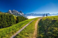 Twee fietsers die de Mythen-pieken in Zwitserse Alpen bekijken stock fotografie