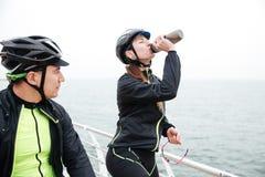 Twee fietsers die dichtbij overzees rusten stock afbeeldingen